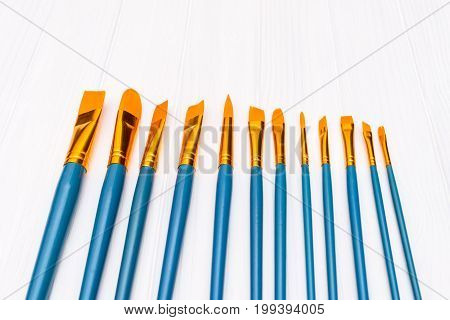 Top view of brushes on the white wooden background. Set of brushes