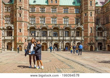 Asian turists in Denmark. Mother and son taking photo with a selfie stick in front of Frederiksborg castle Hillerod Denmark August 6 2017