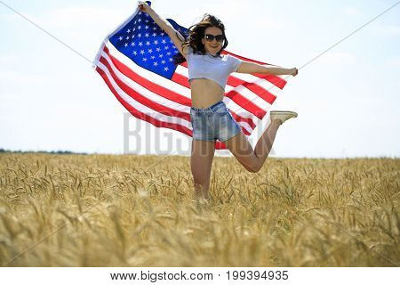Young beautiful brunette woman in jeans shorts with an American flag in a wheat field