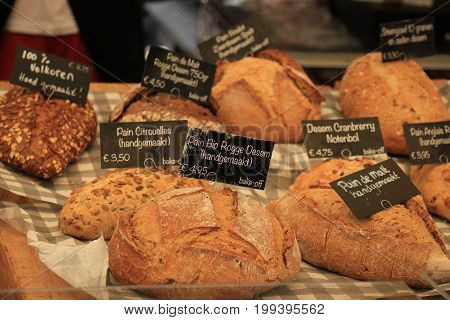 Luxury artisanal bread at a market (text on tags: product and price information in Dutch)
