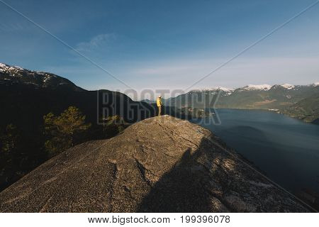 Man Standing On The Top Of Mountains While Sunrise