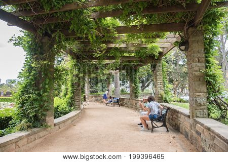 SYDNEY,NSW,AUSTRALIA-NOVEMBER 19,2016: Couple and family resting on benches under the sandstone pergola at Sandringham Gardens with vine growth at Hyde Park in Sydney, Australia.