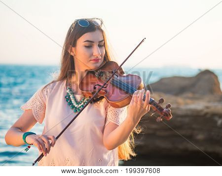 Young beautiful caucasian girl wearing jeans plays violin staying on the beach near the beautiful sea or ocean