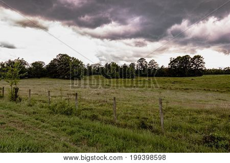 Storm clouds over a pasture with a barbed wire fence in the foreground.