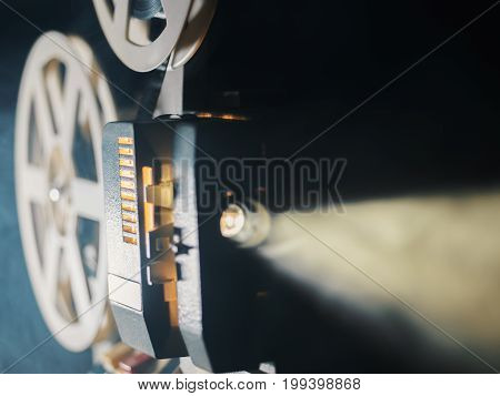 film projector on a black background with dramatic lighting and selective focus