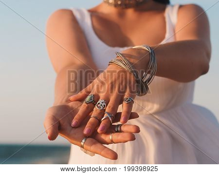close up hands with boho gypsy silver accessories. Woman standing on the beach at summer near sea.