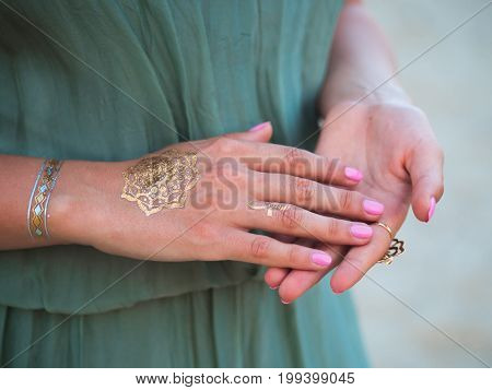 Silver and golden flash tattoo on female hands over sea or ocean background