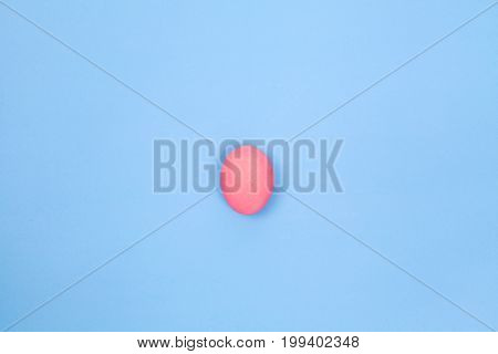 one preserved egg on blue background with space for copy.