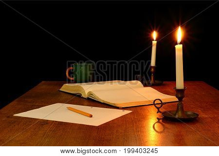 Book Pencil and Paper Illuminated by Candlelight