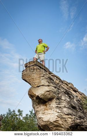 vertical image of a caucasian man on vacation standing at the tip of a tall sandstone rock formation  on a beautiful summer morning.