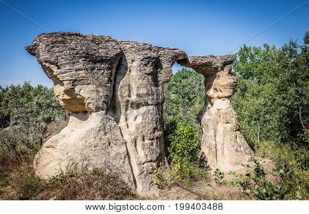 horizontal image of unique sandstone rock formations naturally carved thousands of years ago standing tall under a blue summer sky.