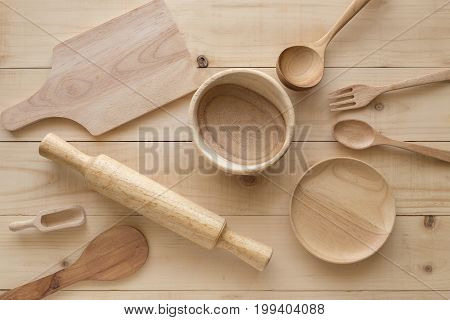 Wooden Rolling Pin And Various Wooden Cooking Utensils On Brown Table