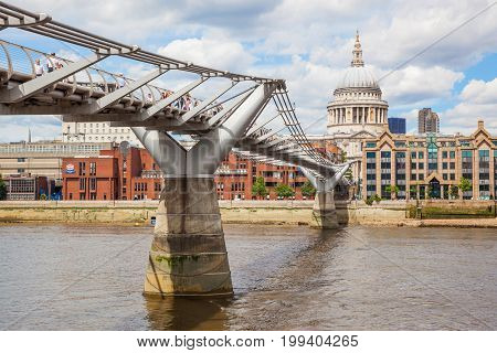 LONDON, UNITED KINGDOM - JUNE 12, 2012: Unidentified pedestrians on the London Millennium Footbridge, a steel suspension bridge crossing the River Thames, with St Pauls Cathedral in the background.