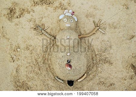 Travel to Phi-Phi island Thailand. A snowman from sand and seashells on a beach.