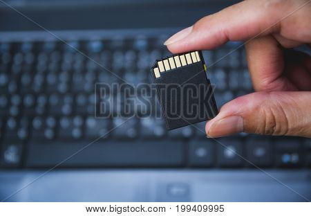 Photographer's hand holding memory card for preparing plug-in to computer.
