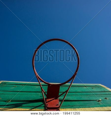 An old basketball ring against the sky. blue sunny