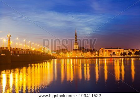 Old Riga night skyline with big stone bridge and St. Peter church. Illuminated city after sunset. Panoramic view over Daugava river