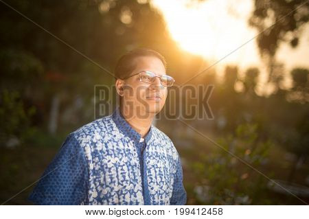 Looking in future with smile. Confident young man keeping away while standing against natural background.