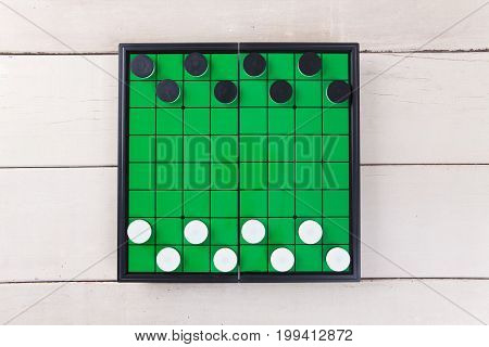 Start Checker Game On Green Board View From Above On Wood Table.