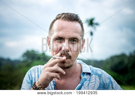 Portrait Of Young Handsome Man Smoking Cigarette Outdoors, Jungle. Bali Island, Indonesia.