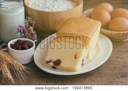 Slices of butter cake on white plate. Homemade butter cake with dried cranberries so delicious soft and moist. Tasty pound cake or butter cake served on wood table. Homemade bakery background concept. Butter cake background concept.