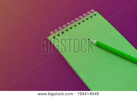 Top view of open spiral blank notebook with pencil on magenta paper background. Open vintage notebook. Empty notebook paper for text with  pencil . office concept top view.Copy space. Space for text.