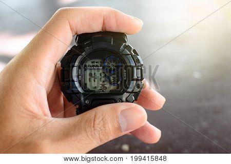 Hand holding black digital clock, digital, watch