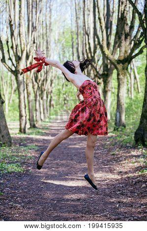 Attractive dancer girl wearing red dress in park