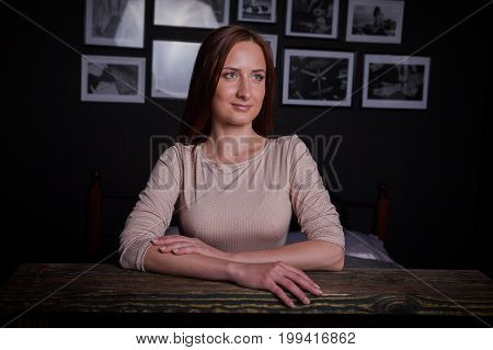Beautiful young woman sitting at vintage wooden table. Wore long classic dress and shoes. Low key studio shot, large portrait with hands.