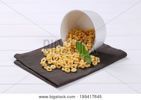 bowl of honey cereal rings spilt out on grey place mat