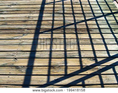 Abstract shadow of steel structure on wooden floor deck creating modern art