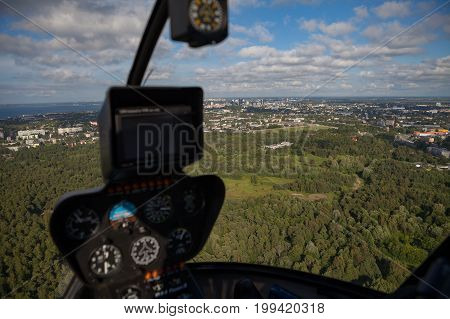 Flying over forest and blurred helicopter cockpit