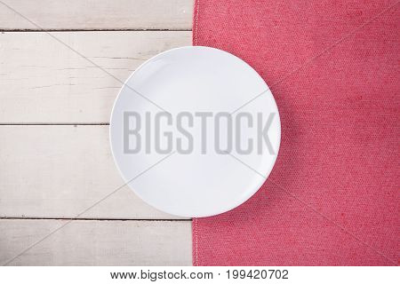 Top View Of Empty White Plate Put On Red Tablecloth And White Wood Table With Space For Copy.