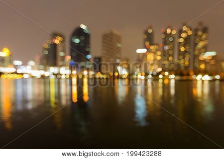 Reflection light water front city office building blurred bokeh light abstract background