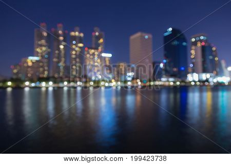 Night blurred bokeh city office building downtown water front abstract background