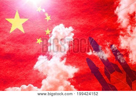 Chinese flag shining through a sunny blue sky background and 3 missiles starting from the right