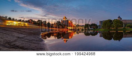 Amazing view with reflection of medieval fortresses on the river Narva at sunset, Estonia and Russia border. Wide panoramic shot