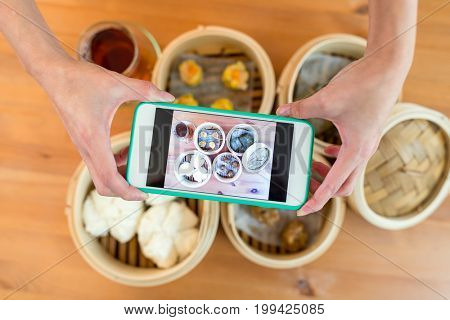 Top view cellphone taking photo on dim sum on chinese restaurant