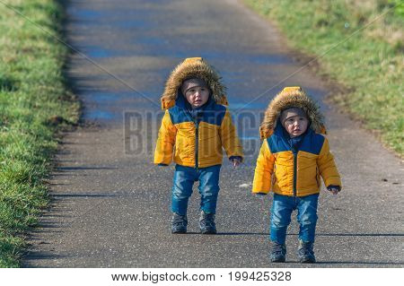 Two small children twins walking on a country road and looking amazed at the camera.