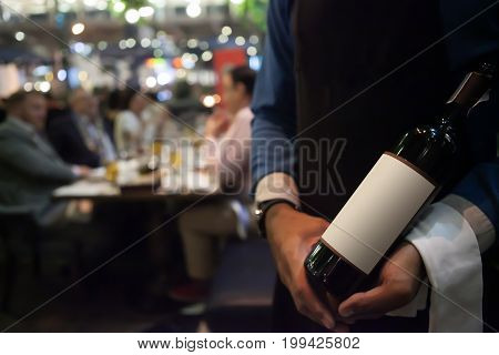 Blurry Background Waiter Holding Wine  On Hand Ready To Serving To Customer In Restaurant.