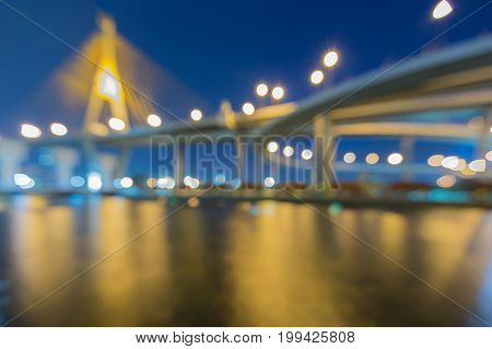 Twilight blurred bokeh light suspension bridge river front abstract background
