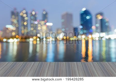 Opening wooden floor City blurred bokeh light with reflection at twilight abstract background