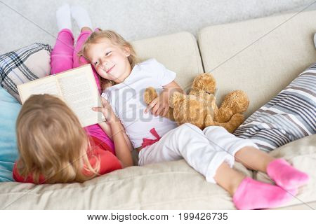 Having fun at home: cute little girl lying on cozy couch and listening to her best friend with interest while she reading fairy tale aloud, high angle view