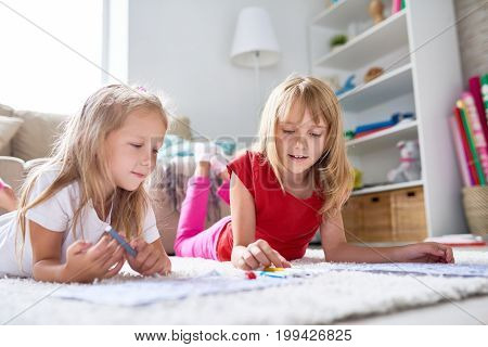 Creative little girls lying on carpet and drawing pictures with felt-tip pens, lovely interior of living room on background