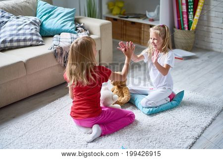 Cheerful little girls playing pat-a-cake while enjoying each others company in cozy living room