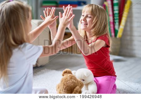 Smiling little friends having fun together while playing pat-a-cake game, interior of cozy modern living room on background