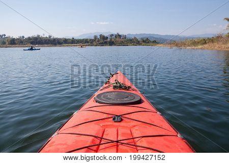 Red Kayak touring on dam in Thailand.