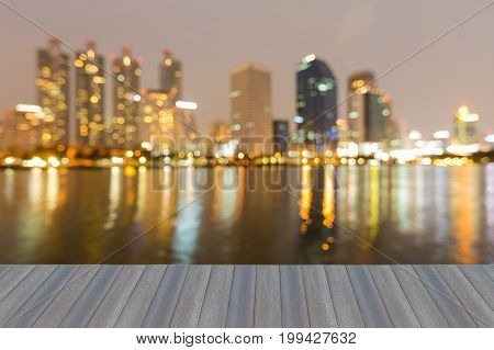 Opening wooden floor Reflection blurred bokeh light city office building water front abstract background