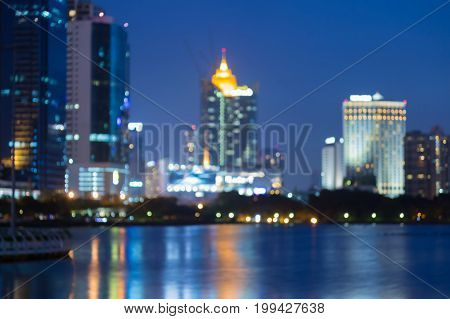 Beautiful night blurred bokeh city office building water front abstract background