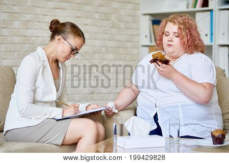 Portrait of female psychologist taking notes on clipboard while consulting obese young woman  eating cupcakes about  mental disorder and health issues